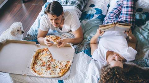 A couple eating pizza and reading a book on a bed