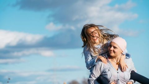 Young woman with cancer talking to her daughter about how to reduce her risk of cancer.