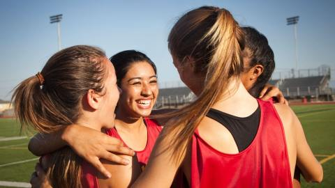 A team of four girls huddling together on a field.