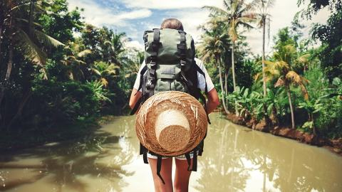 Traveller with a small backpack walking through jungle