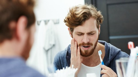 Man in bathroom experiencing pain from not replacing toothbrush