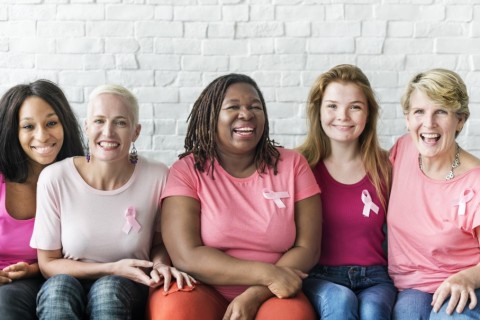 five women wearing pink shirts getting ready for their online health check