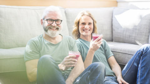 A middle-aged couple sitting against a couch drinking juice