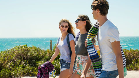 a group of 3 young people walking outside on the way to the beach