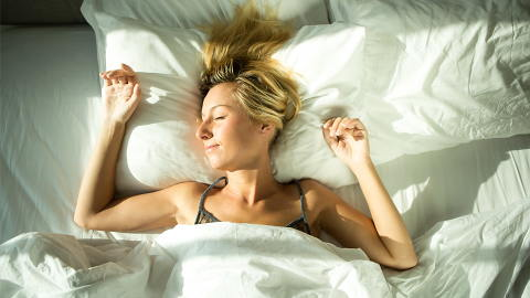 young woman laying in bed and getting extra sleep during winter
