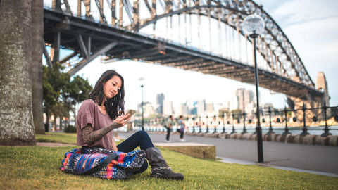 young girl sitting on the grass, looking at phone with the Sydney Harbour Bridge in the Background
