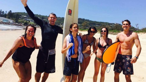 paul harragon, his wife pam and three teens surfing on a beach