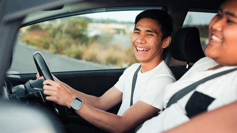 Two male international visitors laughing and driving in Australia