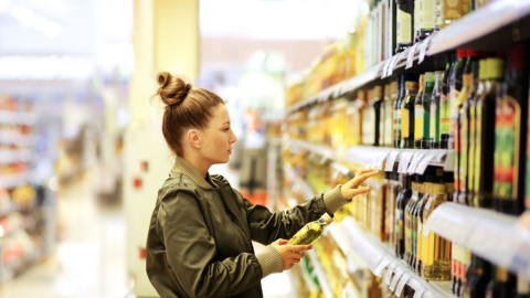 Woman in the supermarket trying to figure out which oil is healthiest - olive, coconut or vegetable