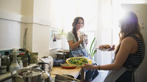 A Woman presenting two plates of food to her friend in the kitchen