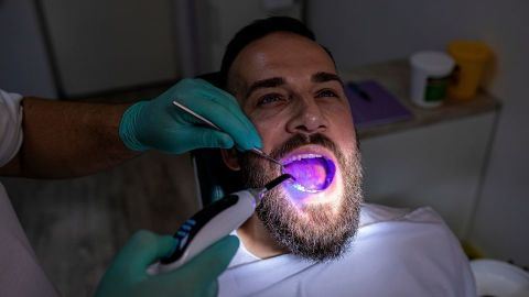 A dentist examining inside a patient's mouth.