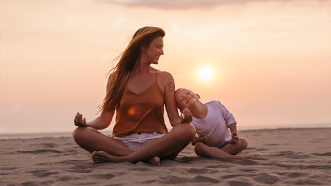 Mother and daughter sitting at the beach meditating together.