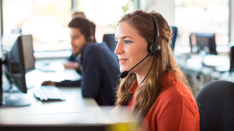 A call centre worker with a headset on the phone