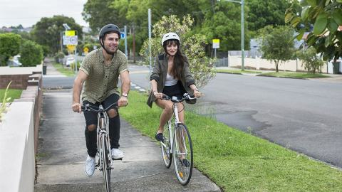 Healthy couple on their bikes riding through the suburb they live in