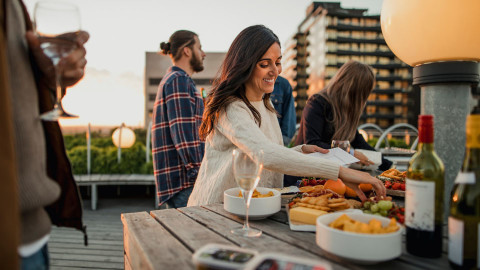 A woman at a rooftop party eating food off a grazing board