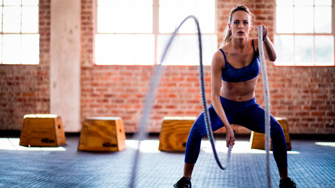 A woman working out at the gym with battle ropes