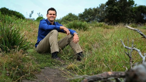 Paul Harragon in a blue shirt sitting on a grassy hill