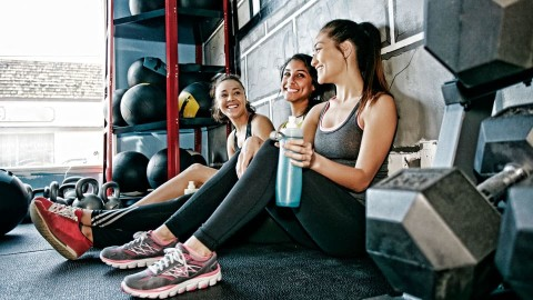 Three girls sitting on a gym floor with their backs against the wall.
