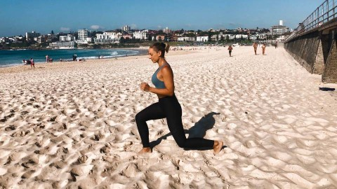 Cassey Maynard doing jump lunges on the beach