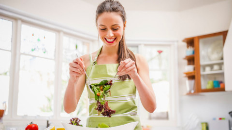 A woman tossing a salad in a kitchen