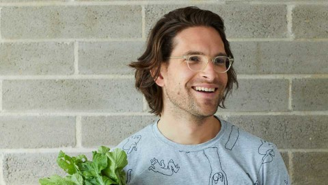 Sandro Demaio with glasses on holding leafy green vegetable in front of a grey brick wall