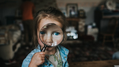 A young girl looking through a magnifying glass.