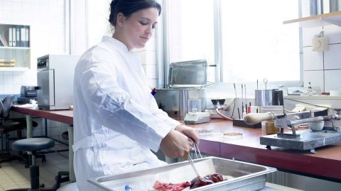 A woman in a lab coat working on high tech food of the future