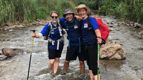 Three nib employees trekking through Borneo water