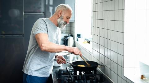 Man cooking on stove in a kitchen