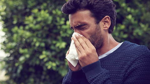 young bearded male with the winter flu blowing his nose
