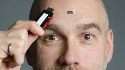 Man plugging usb into foreheard demonstrating nanotechnology