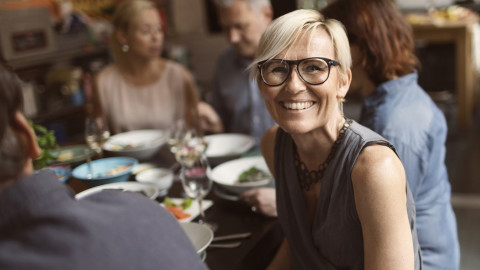 A woman at a dinner party wearing glasses