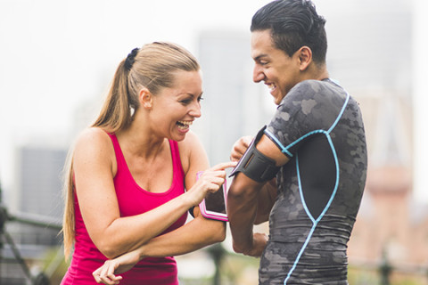Happy, young couple using technology to track their fitness