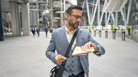 Man walking from the office in his lunch break adn checking the time before he eats