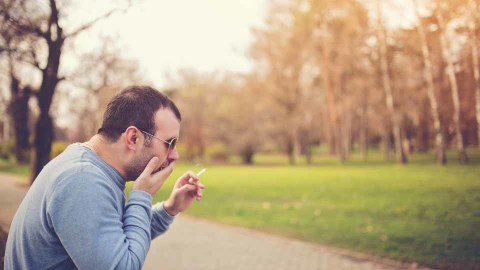 A man smoking and coughing in a park