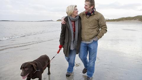 Couple in winter clothing walking their dog on the beach