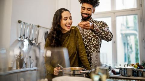 Man holding spoon for Woman to try food they have prepared together