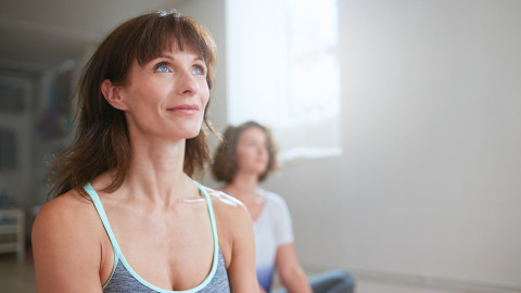 Middle-aged woman practicing yoga and focusing on her health