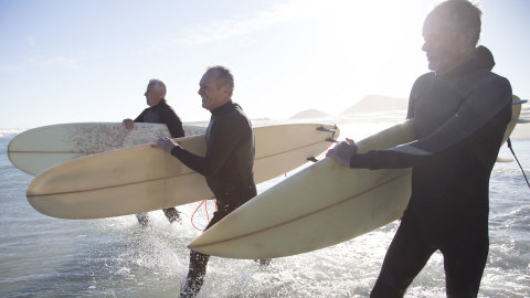 Three men holding surfboards and walking into water