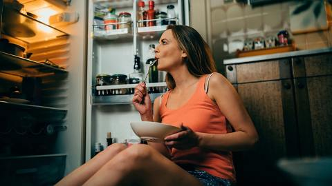 A woman eating food from a bowl near an open fridge