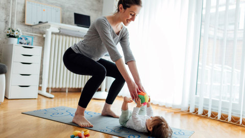 mother practising yoga while tending to her baby.