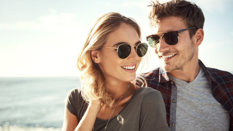 Young couple wearing sunglasses and protecting their eyes from UV damage
