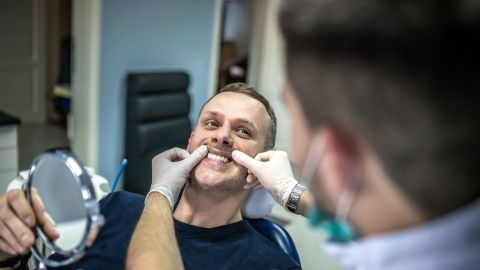 A dentist inspecting a patient's teeth