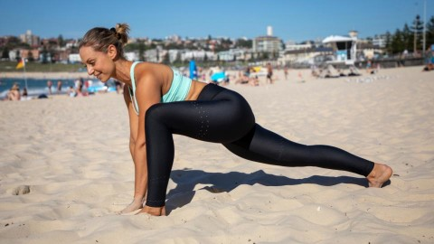 Cassey Maynard stretching on Bondi Beach