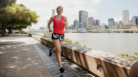 girl running by the river with city in the background