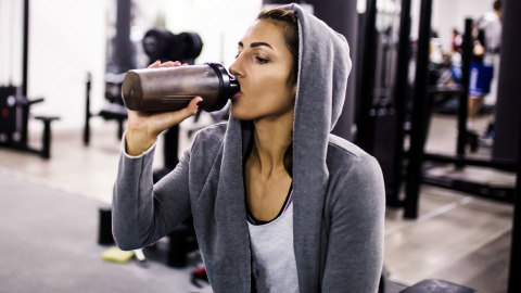 A woman drinking from a protein shake bottle