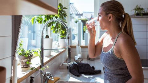 young blonde woman drinking water from her kitchen tap
