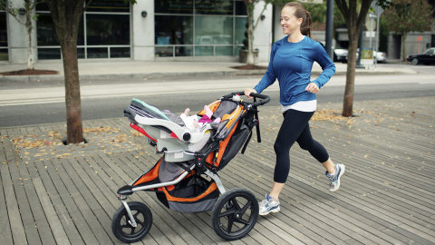 Woman running outdoors in the city with a pram