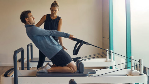 Woman instructing man on using pilates device