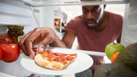 Man looking in his fridge at a piece of pizza to see if the leftovers are still edible.